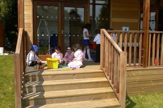 Children on the Decking of their Eco Classroom at Danesfield Manor School by The Learning Escape
