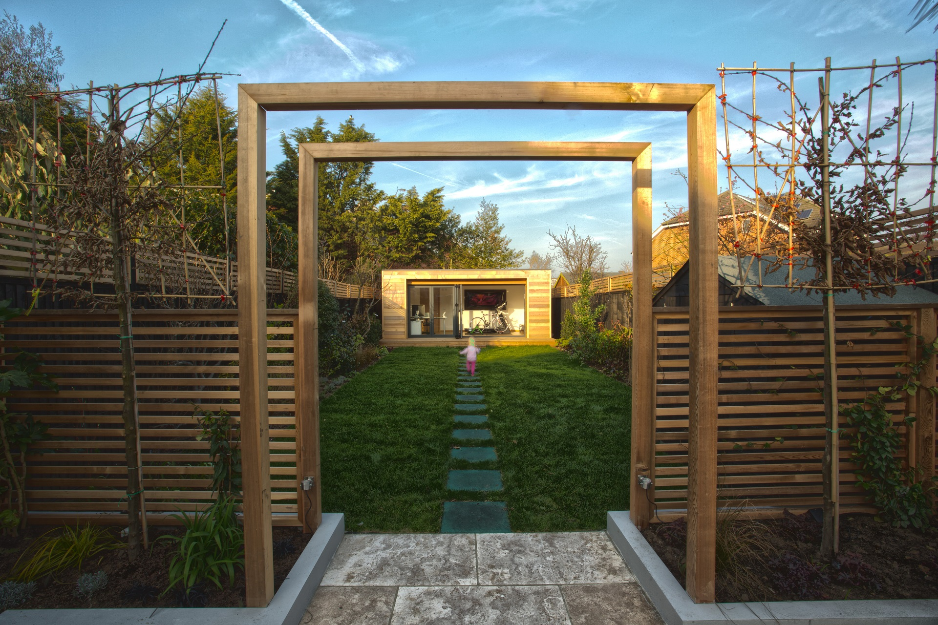 Two fence arches framing an eco garden office  building